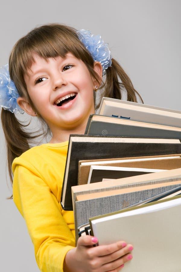Pilha da terra arrendada da menina de livros fotografia de stock