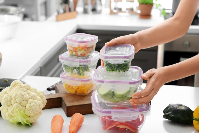 Pilha da terra arrendada da mulher de recipientes plásticos com os legumes frescos para congelar-se na tabela na cozinha foto de stock
