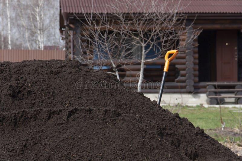 Pilha da terra f?rtil no fundo da casa da vila imagem de stock