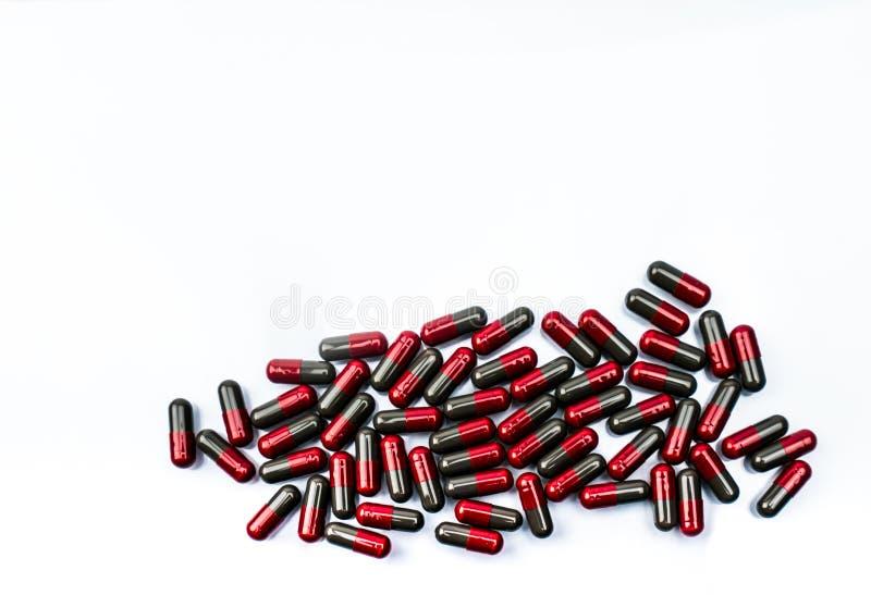 Pilha da vista superior dos comprimidos vermelhos e cinzentos da cápsula isolados no fundo branco com espaço da cópia Flunarizine foto de stock