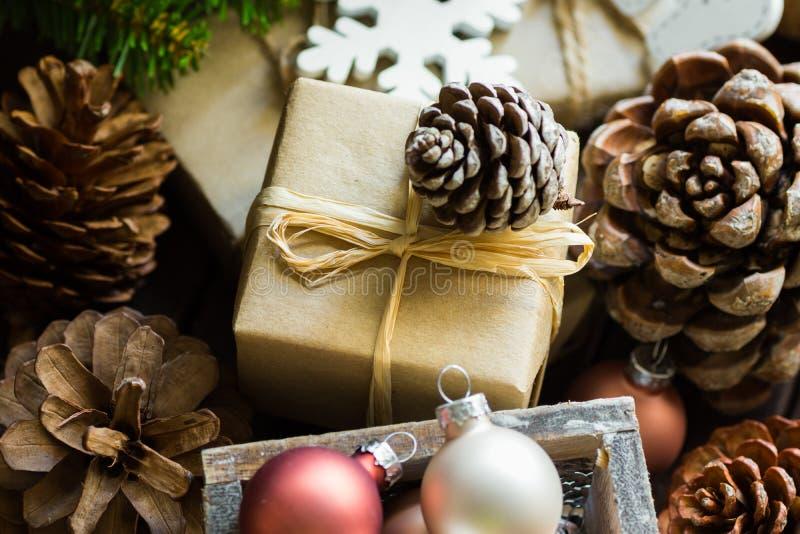 Pilha das caixas de presente envolvidas no papel marrom do ofício, cones do Natal e do ano novo do pinho, ramos de árvore do abet imagens de stock