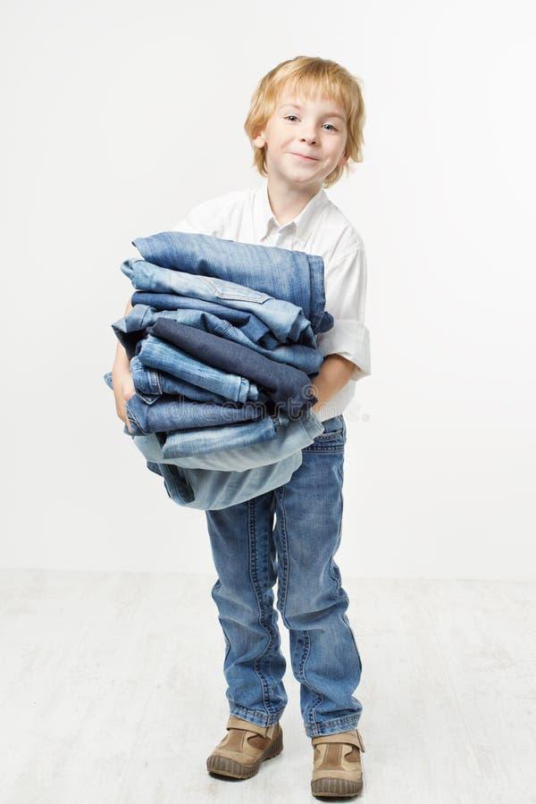 Pilha das calças de brim da terra arrendada da criança. Miúdos que vestem a forma foto de stock royalty free