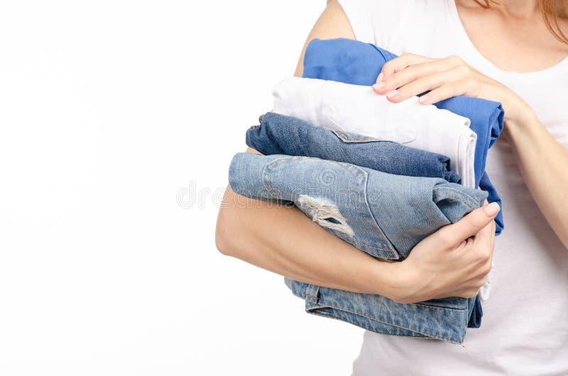 Pilha das calças de brim nas mãos de uma mulher foto de stock royalty free