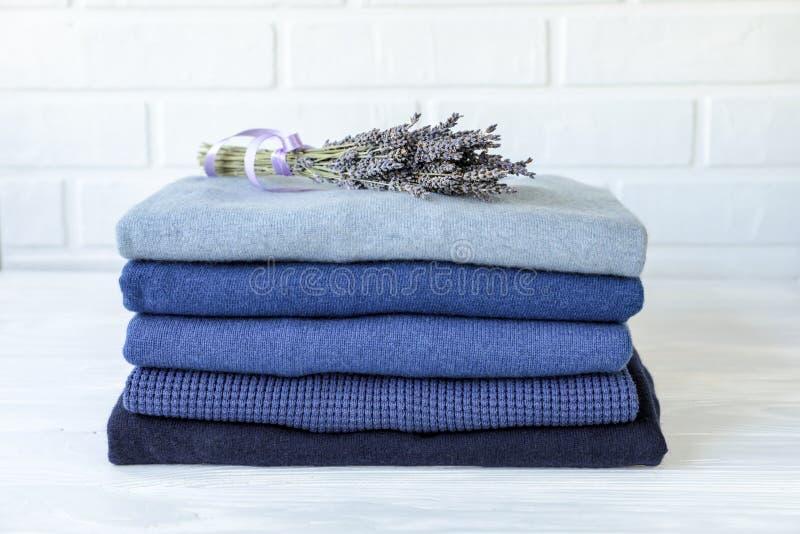Pilha das camisetas dos homens feitos malha mornos dobrados no azul e em um grupo da alfazema secada, cuidado do aroma da roupa e imagem de stock