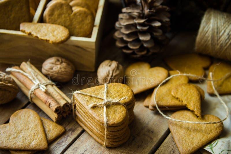 Pilha das cookies do Natal do pão-de-espécie na forma do coração amarradas com guita, varas de canela, porcas, cones do pinho na  fotografia de stock