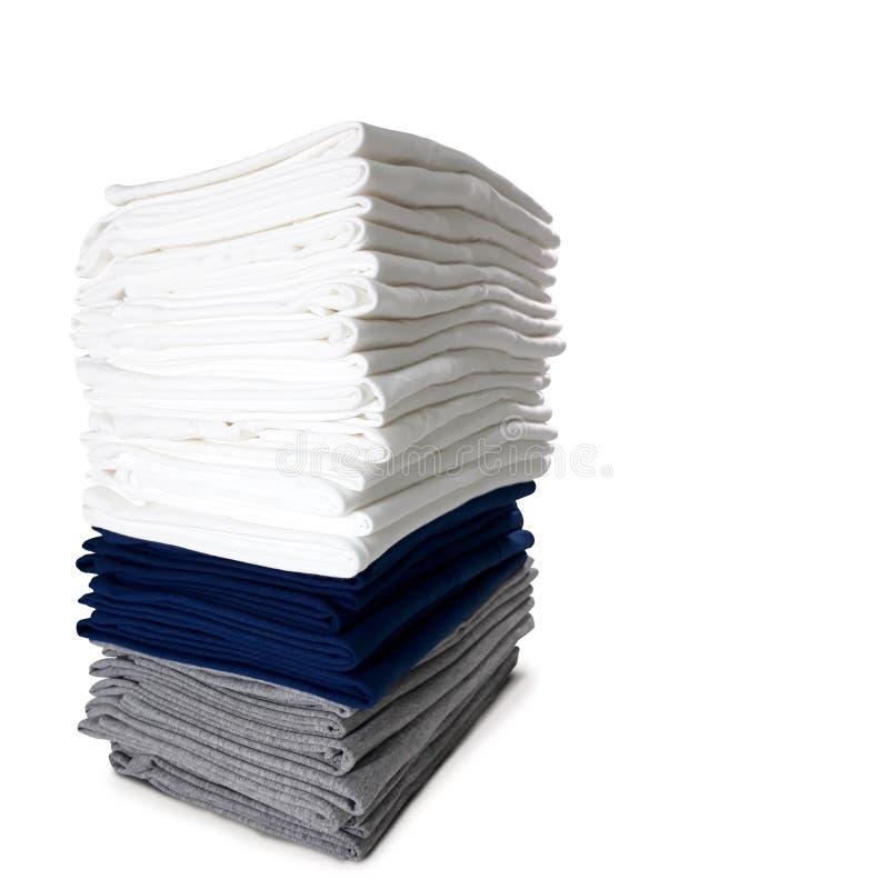 A pilha das cores dobrou os t-shirt isolados no fundo branco - fim acima Trajeto de grampeamento imagem de stock royalty free