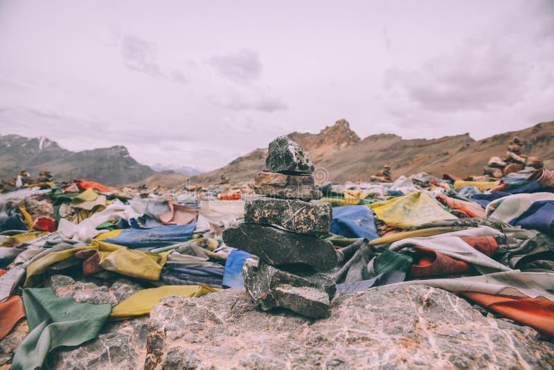 pilha das pedras e de bandeiras coloridas da oração no pico de montanha em Himalayas indianos, imagem de stock