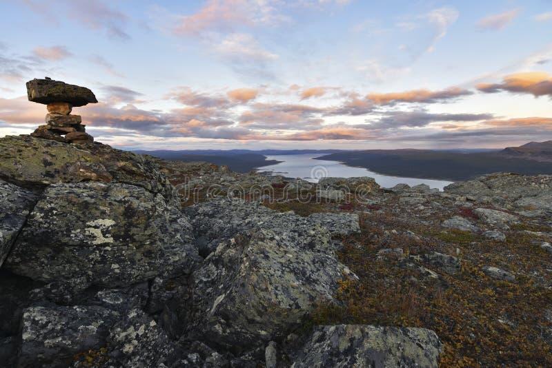 A pilha das pedras marca a parte superior da montanha, o por do sol bonito e o fundo do lago imagem de stock