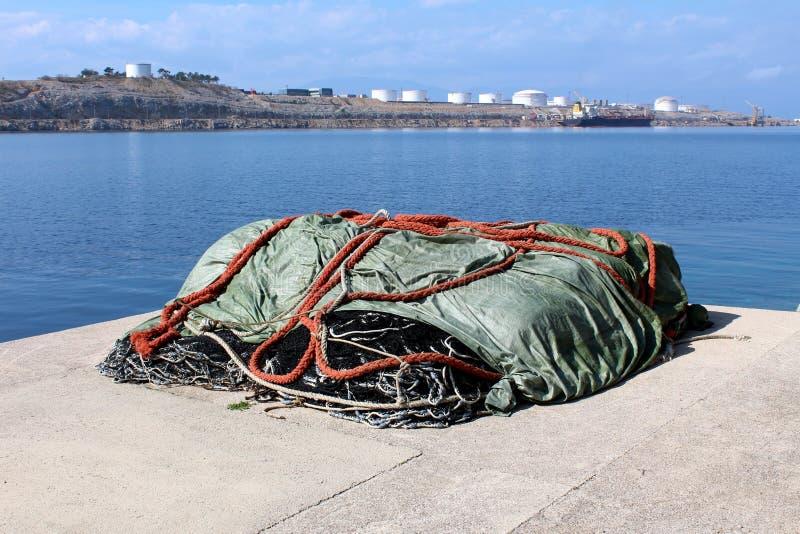 Pilha das redes de pesca cobertas com a proteção de nylon durante o inverno na borda concreta do cais cercada com mar e complexo  foto de stock