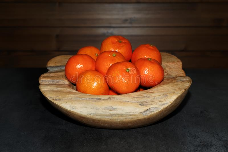 Pilha das tangerinas em uma bacia de madeira na tabela escura imagem de stock