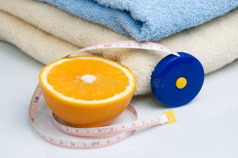 Pilha das toalhas, da medida de fita e da laranja fotografia de stock