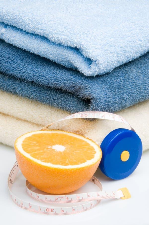 Pilha das toalhas, da medida de fita e da laranja foto de stock