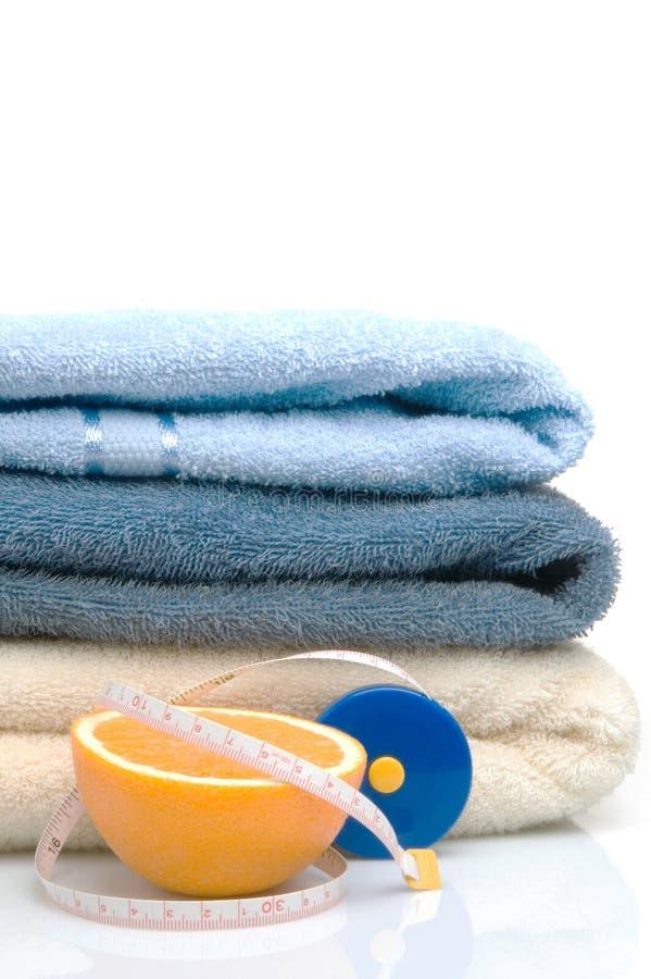 Pilha das toalhas, da medida de fita e da laranja imagens de stock royalty free