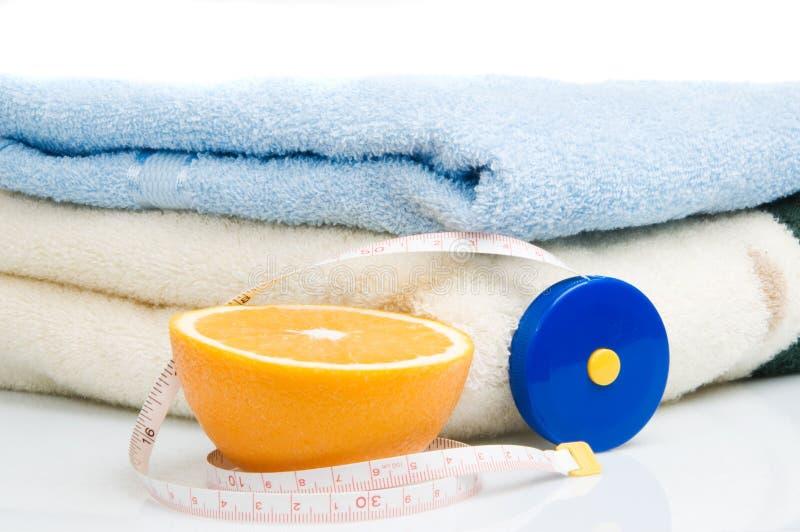 Pilha das toalhas, da medida de fita e da laranja imagem de stock