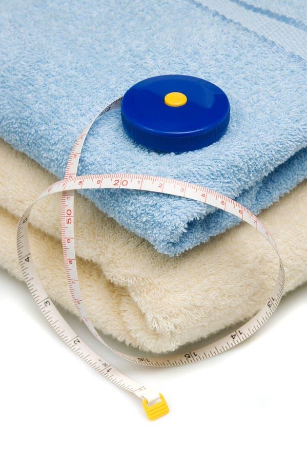 Pilha das toalhas e da medida de fita fotografia de stock