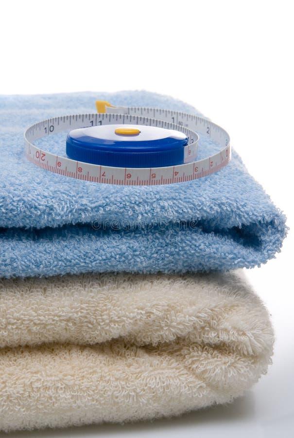 Pilha das toalhas e da medida de fita fotografia de stock royalty free