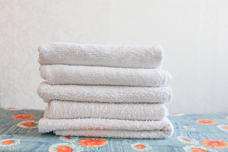 Pilha das toalhas limpas brancas no fundo branco Roupa passando na tábua de passar a ferro Pilha de toalhas limpas na tabela imagens de stock