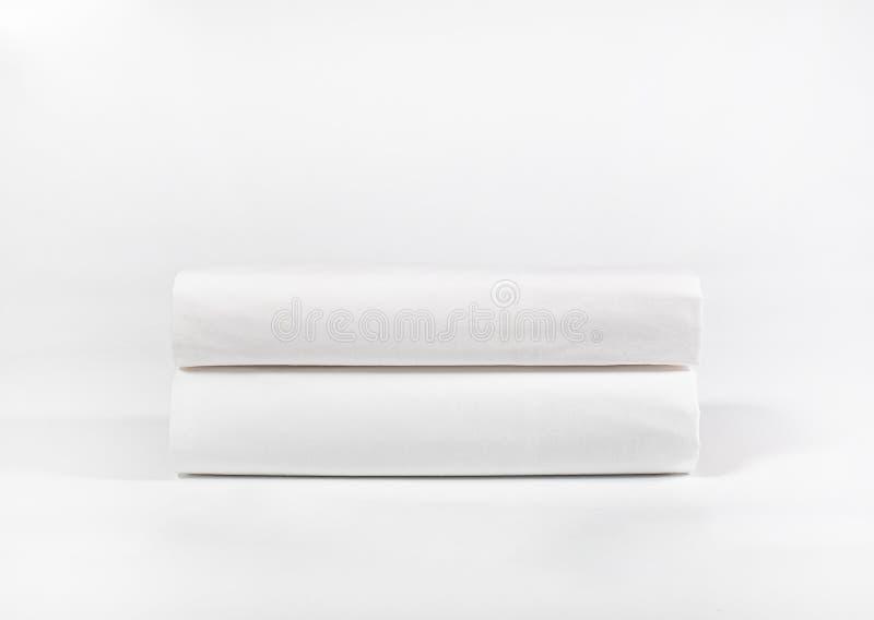 Pilha das toalhas ou das folhas brancas dos termas contra o contexto branco fotografia de stock royalty free