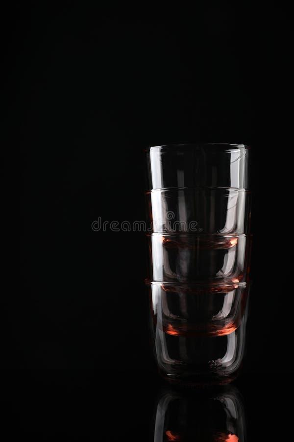 Pilha de óculos de whiskey coloridos vazios em preto, espaço para texto imagem de stock