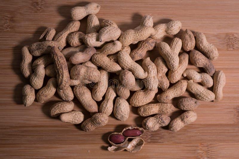 Pilha de amendoins unshelled crus no fundo de madeira natural fotos de stock royalty free