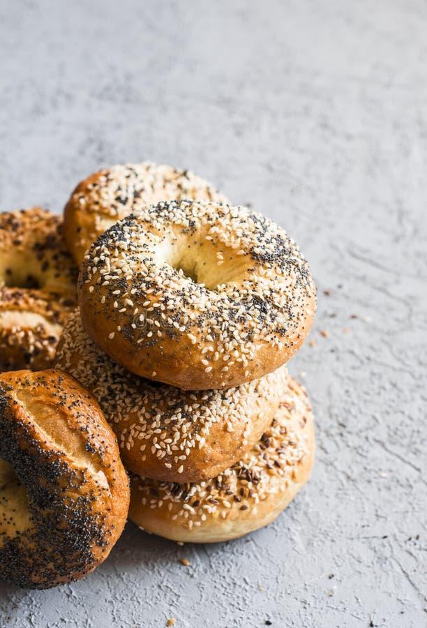 Pilha de bagels caseiros com uma variedade de sementes em um fundo cinzento Café da manhã ou petisco delicioso foto de stock