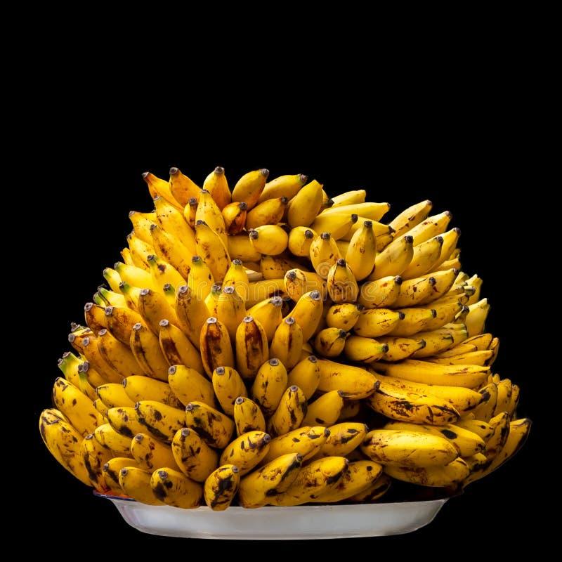 Pilha de bananas amarelas em uma placa branca no fundo preto imagens de stock