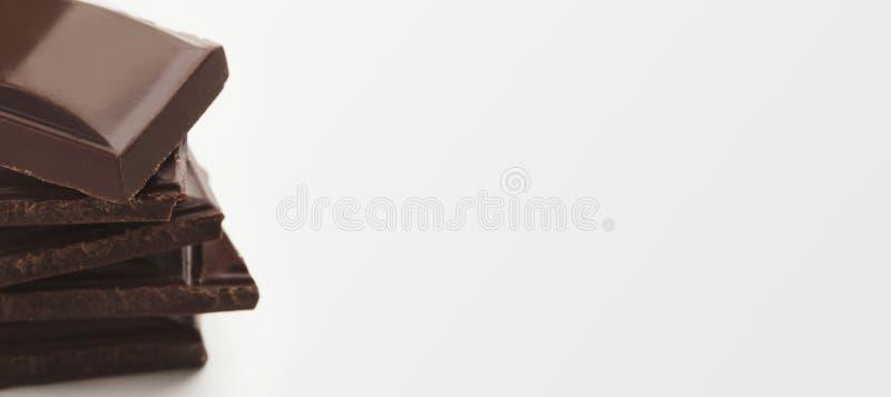 Pilha de barras de chocolate escuras no fundo branco imagens de stock