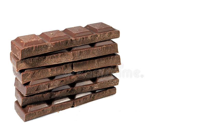 Pilha de barras de chocolate escuras acima rachadas isoladas no fundo branco com espaço livre para o texto foto de stock
