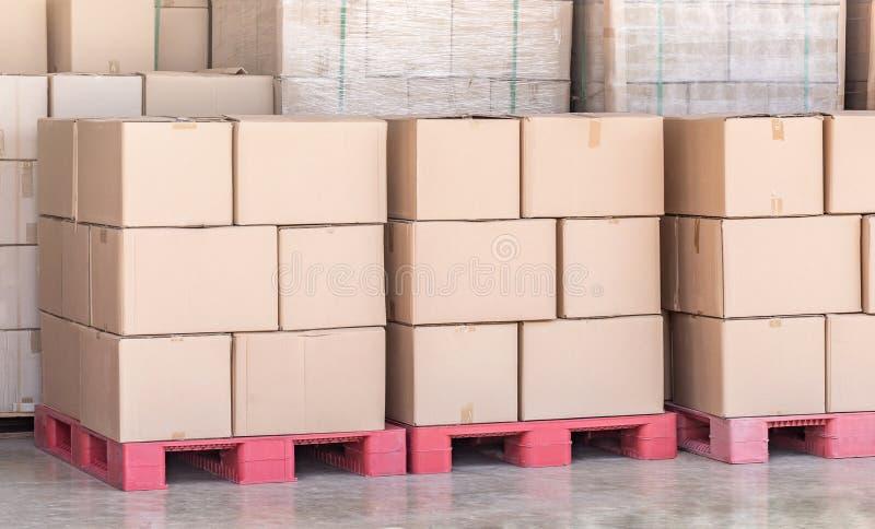A pilha de bens encaderna caixas na pálete vermelha no armazém da logística fotos de stock royalty free
