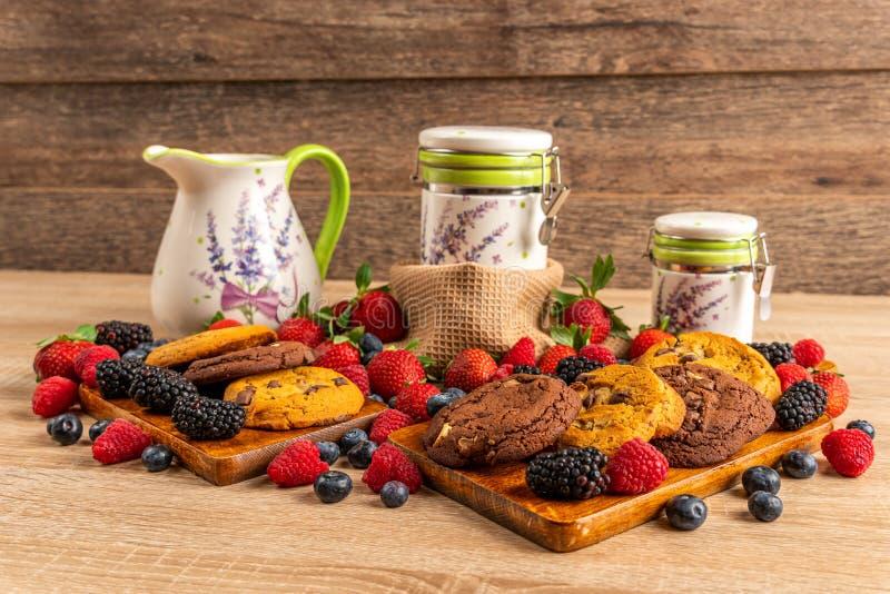 Pilha de biscoitos e de frutos da floresta na placa de corte de madeira fotografia de stock royalty free