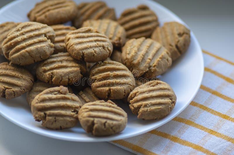 Pilha de biscoitos de manteiga de amendoim em uma placa branca, doces cozidos dourados muito saborosos, biscoitos servidos para c fotografia de stock