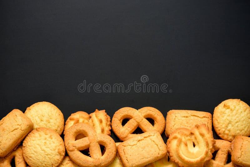 Pilha de biscoitos de manteiga dinamarqueses em forma diferente no fundo da placa preta, espaço de cópia foto de stock
