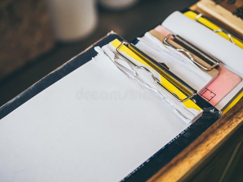 Pilha de bloco de notas vazio rasgada na prancheta para a lista da ordem da nota em uma cafetaria ou em um restaurante imagens de stock
