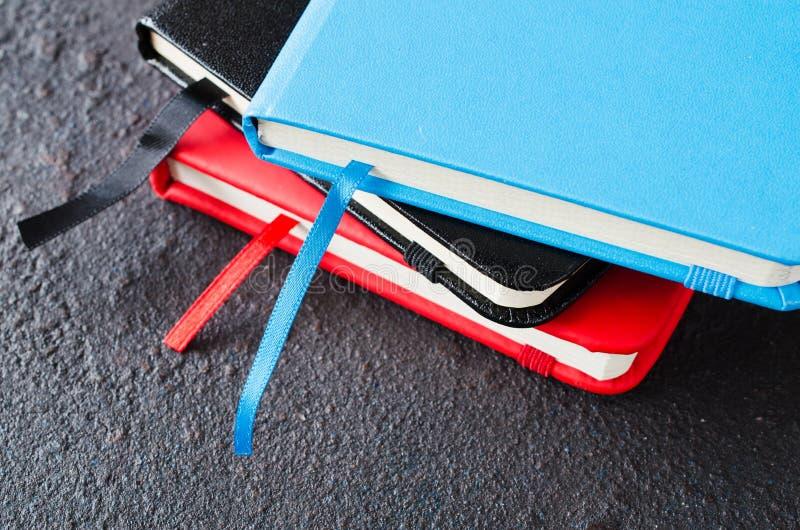 Pilha de cadernos coloridos para escrever ou de livros no fundo escuro fotos de stock royalty free