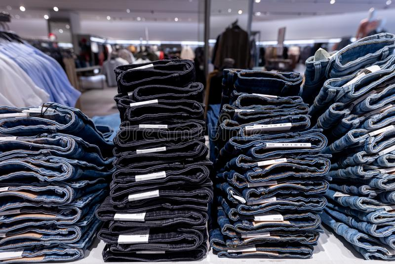 Pilha de calças de brim na loja elevadores, vidro e metal Conceito da compra fotos de stock royalty free