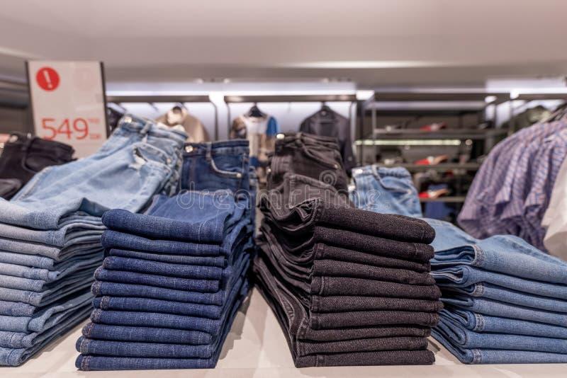 Pilha de calças de brim na loja elevadores, vidro e metal Conceito da compra fotos de stock
