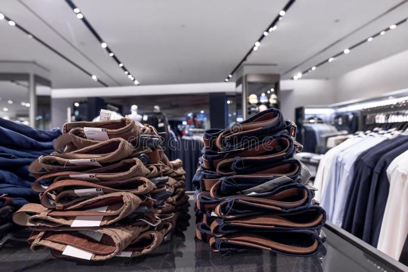 Pilha de calças de brim na loja elevadores, vidro e metal Conceito da compra fotografia de stock