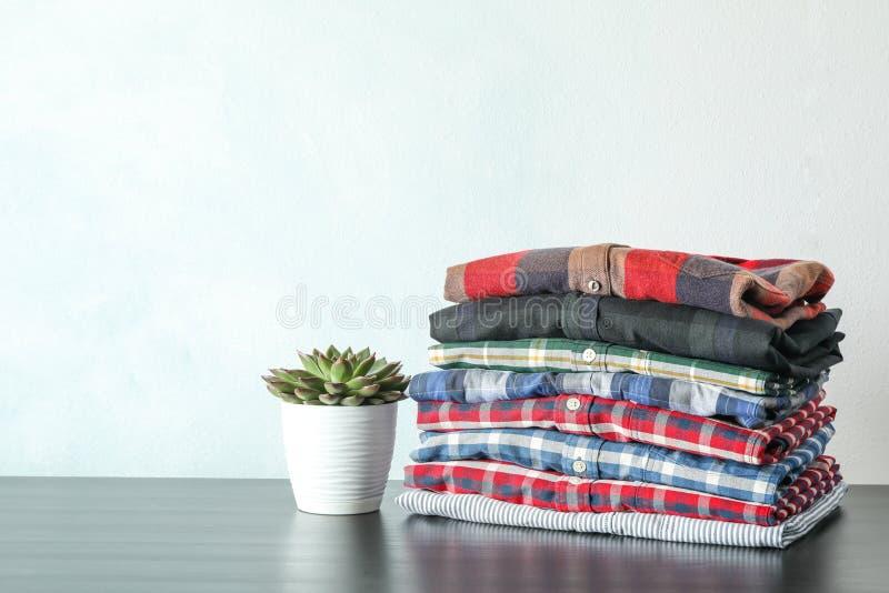 Pilha de camisas coloridas e de planta suculento na tabela fotografia de stock