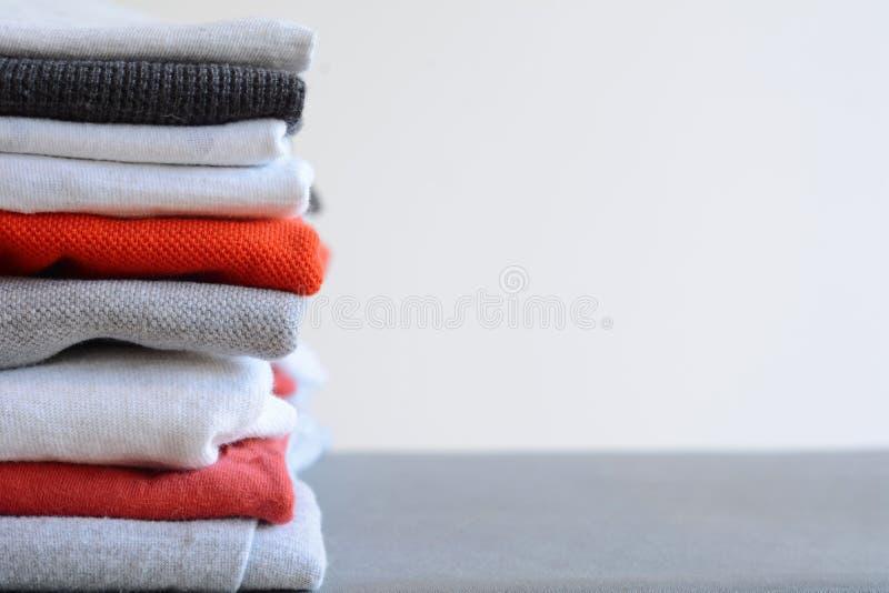 Pilha de camisas dobradas coloridas na tabela cinzenta imagem de stock royalty free