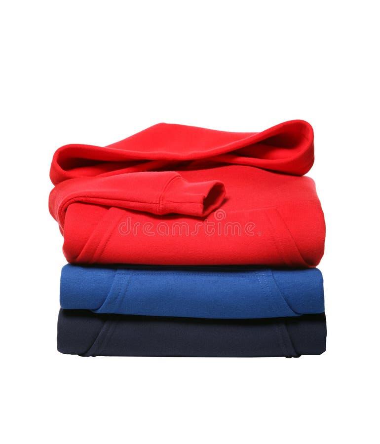 Pilha de camisas suadas encapuçados dobradas isoladas no fundo branco imagens de stock