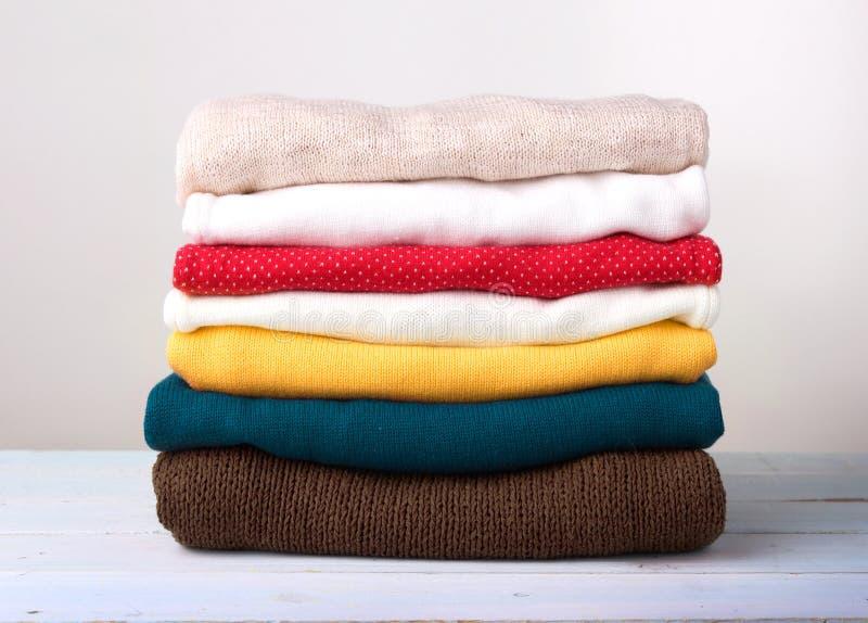 Pilha de camiseta dobrada feita malha da roupa na madeira fotografia de stock royalty free