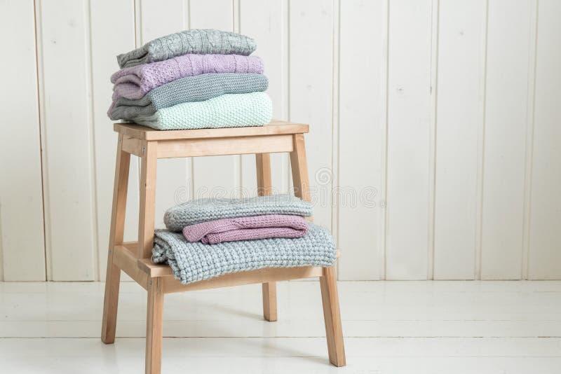 Pilha de camisetas feitas malha acolhedores em uma escada de madeira Estilo escandinavo fotos de stock