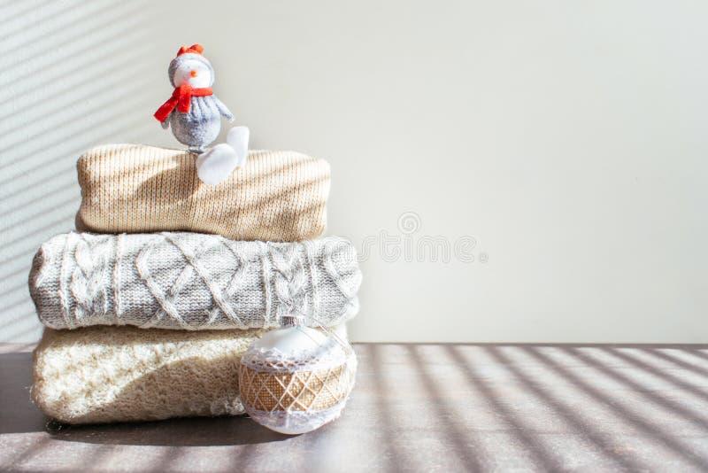Pilha de camisetas feitas malha mornas com ornamento do Natal e boneco de neve do brinquedo na tabela de madeira no fundo claro fotografia de stock