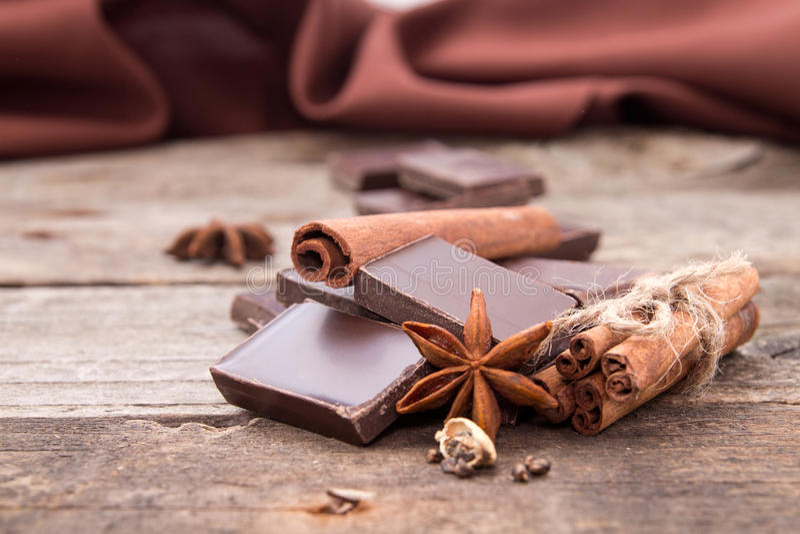 A pilha de chocolate rachou partes com canela, estrela do anis imagens de stock