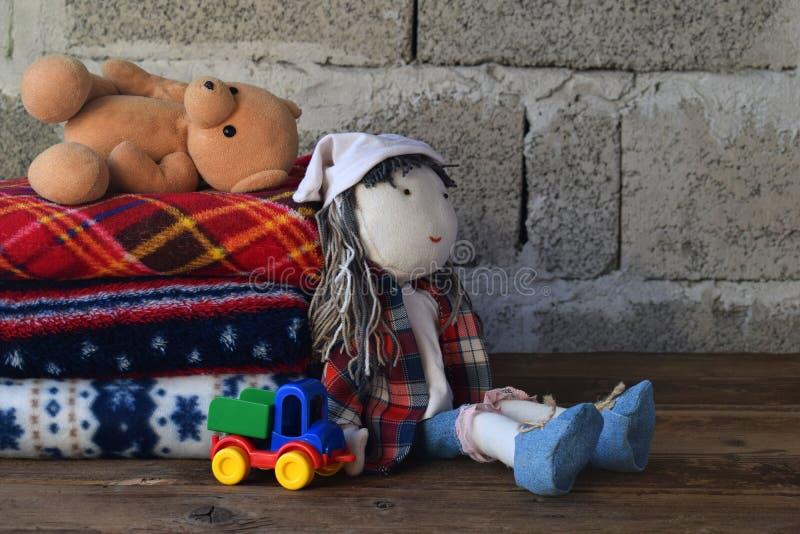 Pilha de coberturas e de boneca de lã mornas no fundo de madeira Brinquedos da matéria têxtil das crianças Cosiness home Brinqued imagem de stock