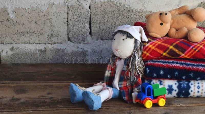 Pilha de coberturas e de boneca de l? mornas no fundo de madeira Brinquedos da mat?ria t?xtil das crian?as Cosiness home Brinqued fotos de stock