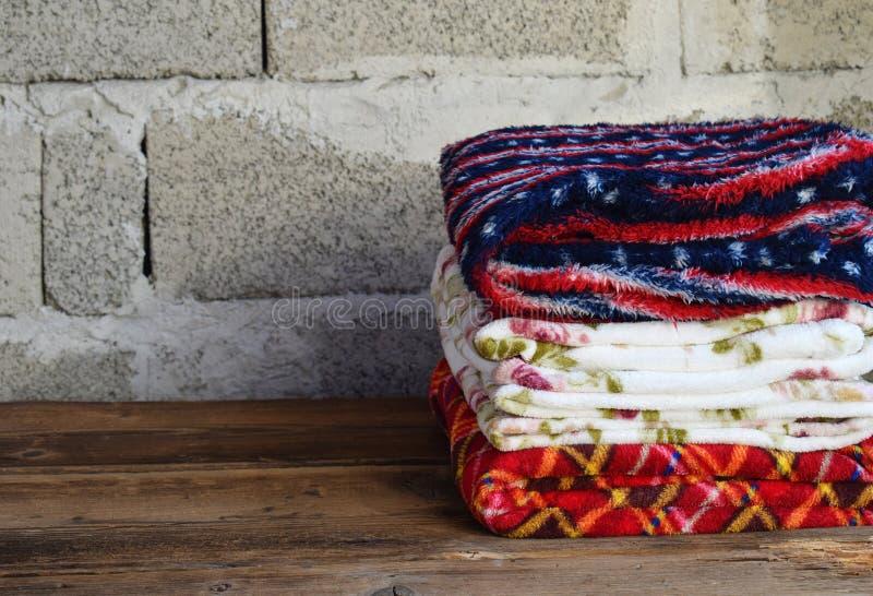 Pilha de coberturas de lã mornas no fundo de madeira Cosiness home Mantas coloridas fotos de stock