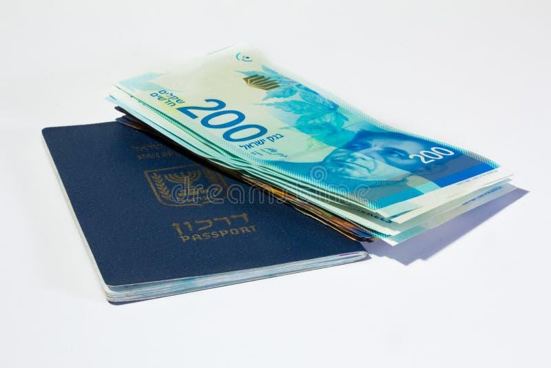 Pilha de contas de dinheiro israelitas do shekel 200 e do passaporte do israelita fotografia de stock