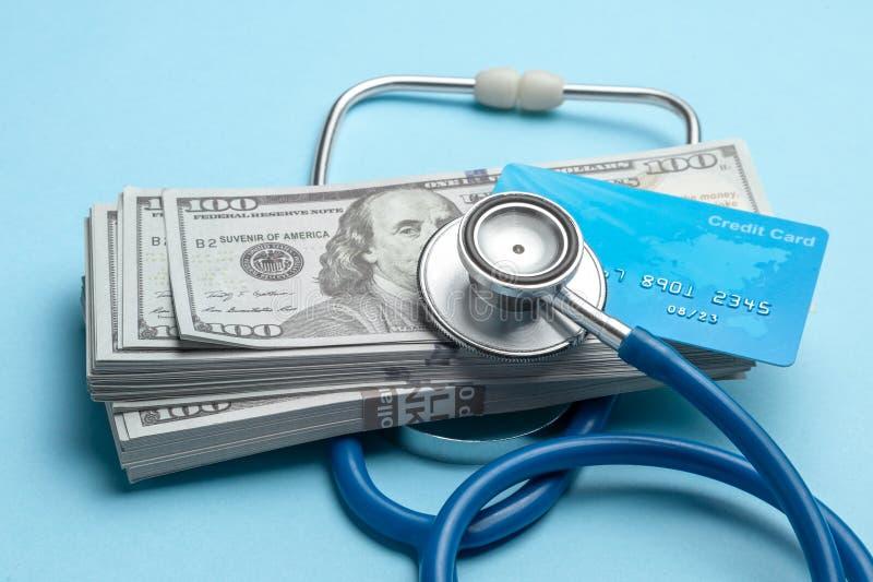 Pilha de dólares do dinheiro e de cartão de crédito com o estetoscópio no fundo azul O conceito do strechevka médico ou da medici imagens de stock royalty free