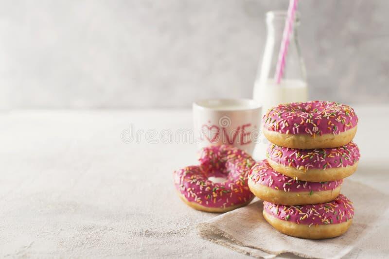 Pilha de donats cor-de-rosa e brancos com a garrafa do leite sobre os vagabundos brancos foto de stock royalty free